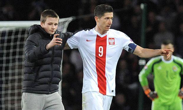Robert Lewandowski of Poland with a pitch invading Scotland fan taking a selfie that might have cost / Bild: (c) imago/BPI (imago sportfotodienst)